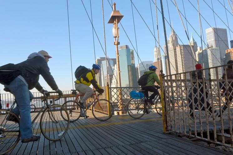 Viajeros en bicicleta cruzan un puente en la ciudad de Nueva York. Conducir con menos frecuencia es una forma de reducir su impacto personal en el clima.