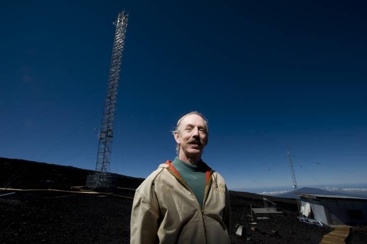 Un científico cerca de una torre de observación meteorológica en Hilo, Hawaii.