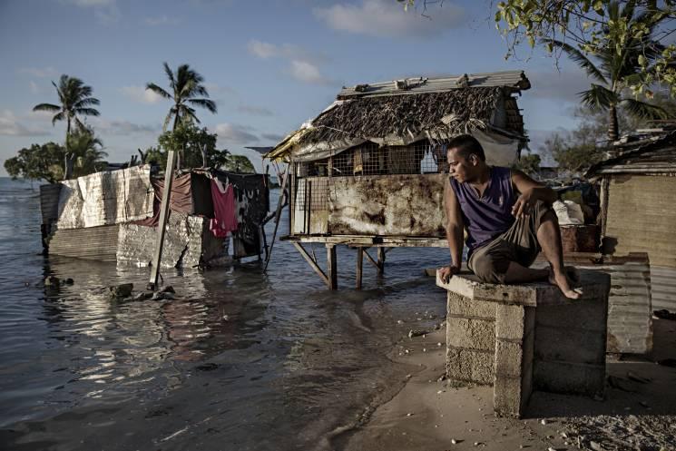 Un residente de la aldea de Eita en Kiribati observa cómo el océano inunda su ciudad natal. La isla se encuentra a pocos pies sobre el nivel del mar, lo que la pone en riesgo de inundaciones y marejadas.