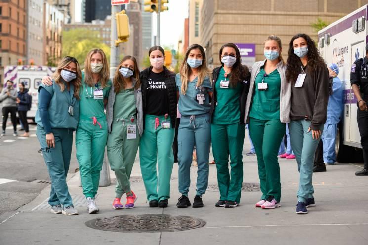 group of medical workers stand shoulder to shoulder