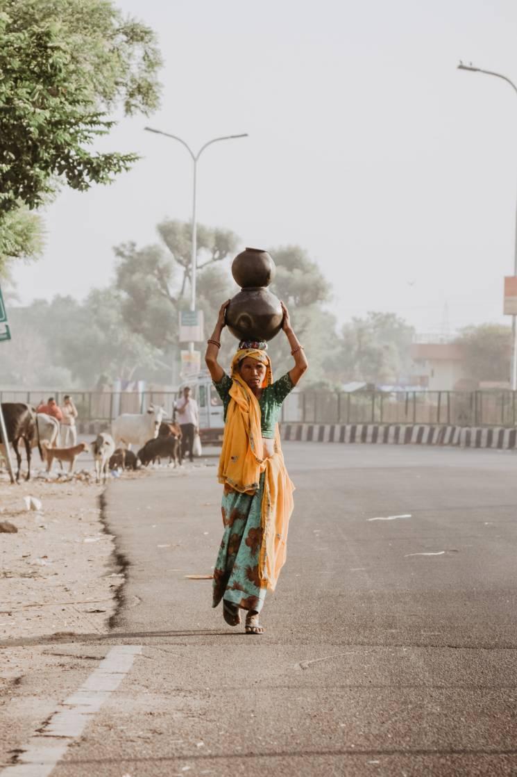Una mujer lleva agua a su casa;; Ibrahim Rifath on Unsplash