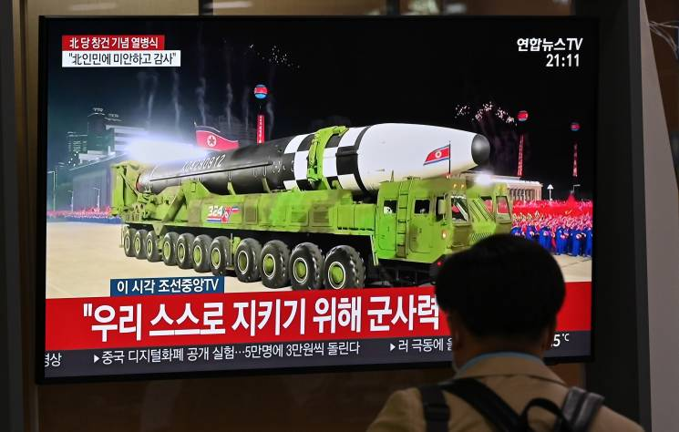 man watches TV broadcast with image of a missile