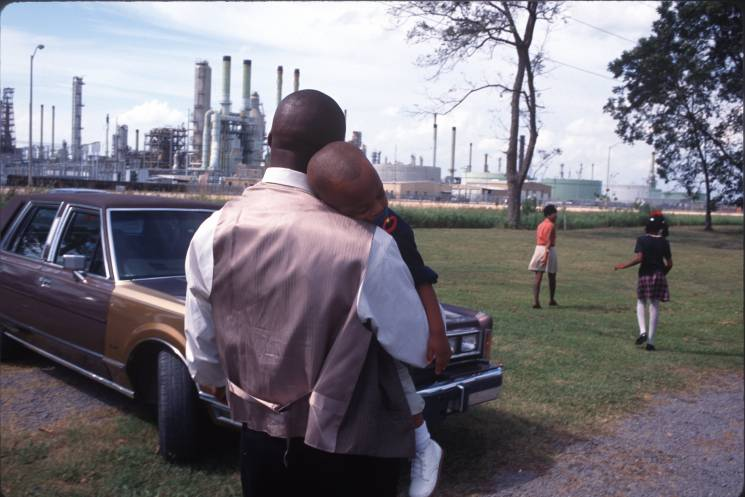 A family leaves Sunday church services surrounded by chemical plants in October of 1998 in Lions, Louisiana. The poor, often black towns along the Mississippi River near Baton Rouge are known as