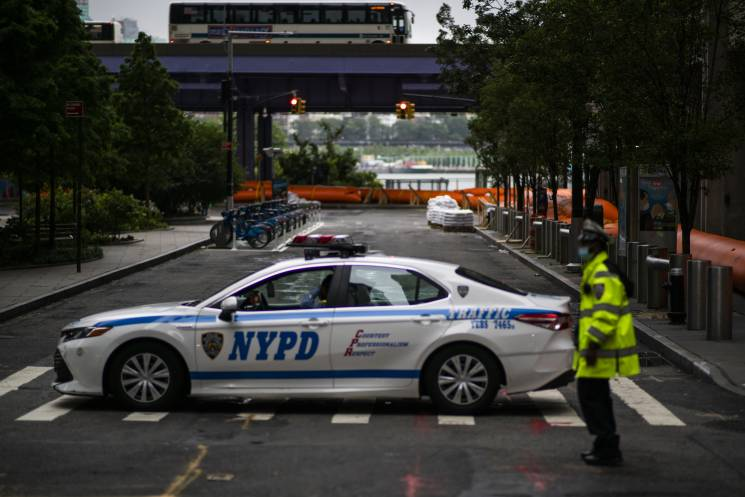 NYPD officers stand guard next to flood barriers used to prevent flooding at the South Street Seaport as the city gets ready for tropical storm Isaias on August 4, 2020 in New York City. The storm, which is heading up the East Coast, is expected to dump several inches of rain with heavy winds into the New York City area starting late Monday evening and into Tuesday. The interlocking tubes called Tiger Dams are installed in areas that were heavily damaged from flooding during Hurricane Sandy.; Getty