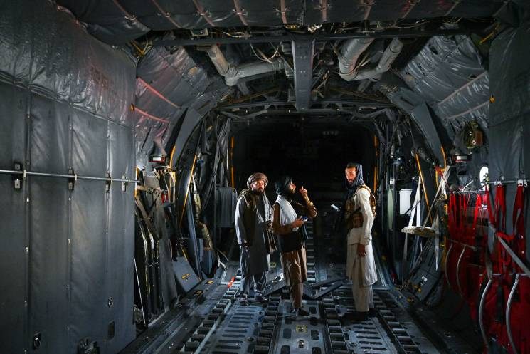 group of Afghan men stand inside an empty aircraft