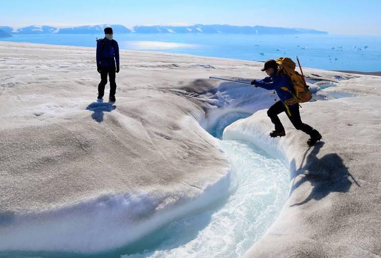 Scientists cross a river on a glacier