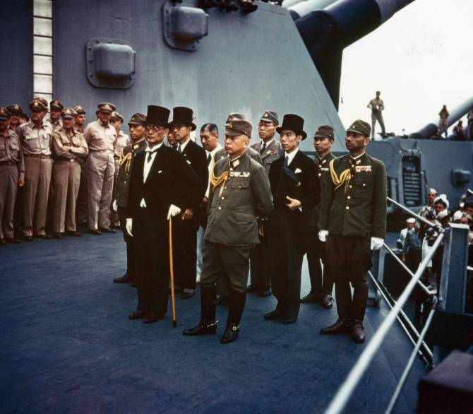 A group of Japanese men in military dress and suits stand in a tight group aboard the deck of a battleship.