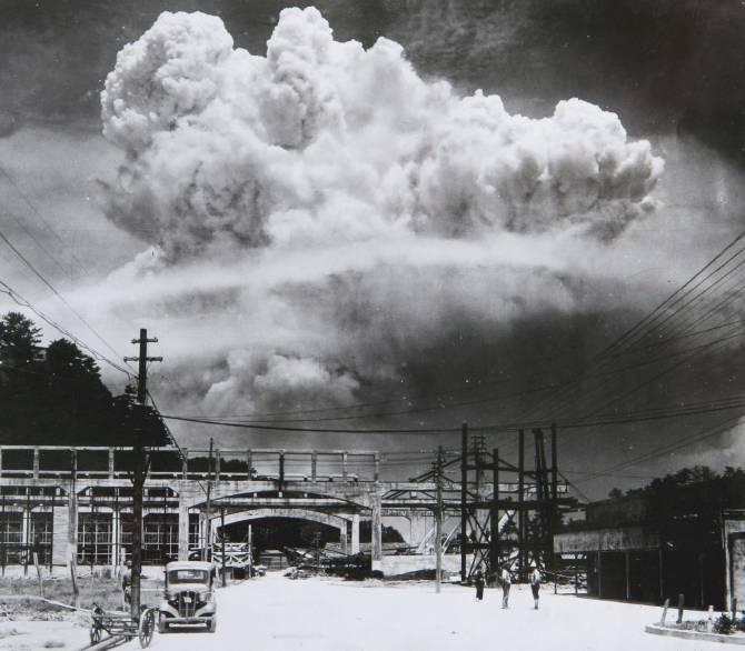 A huge mushroom cloud is seen beyond a desolate looking road.