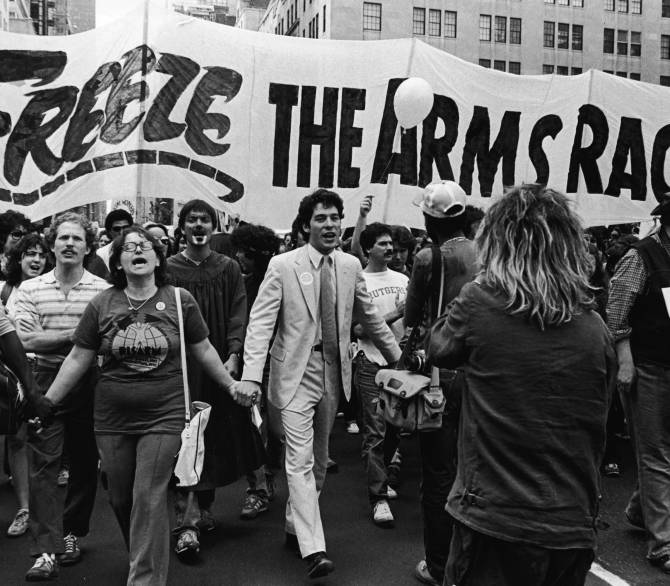 A group of people march in front of a sign that reads 'Freeze the arms race'.