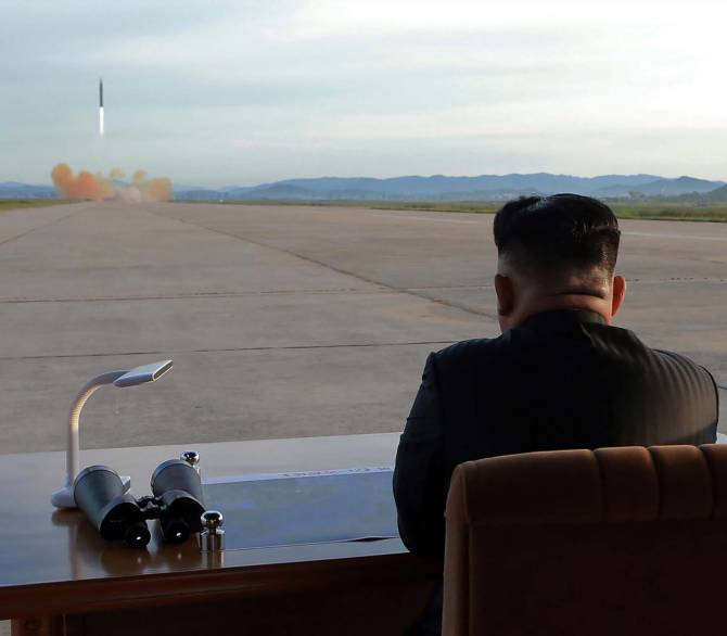 Kim Jong Un sits at a desk in the middle of an airfield, watching a missile launch in the distance.