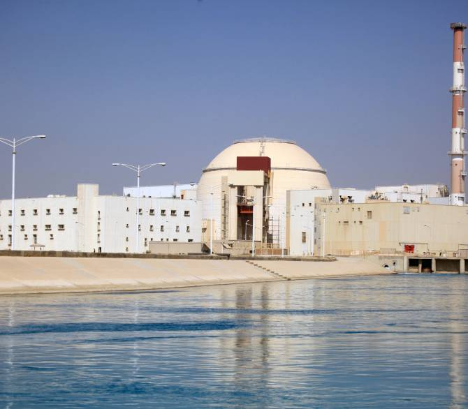 A tan and white domed building with a smokestack sits behind a body of water.