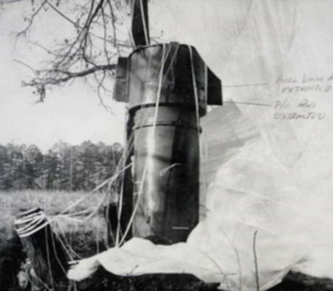 An unexploded bomb with a parachute sticks out of the ground in a field near a forest.