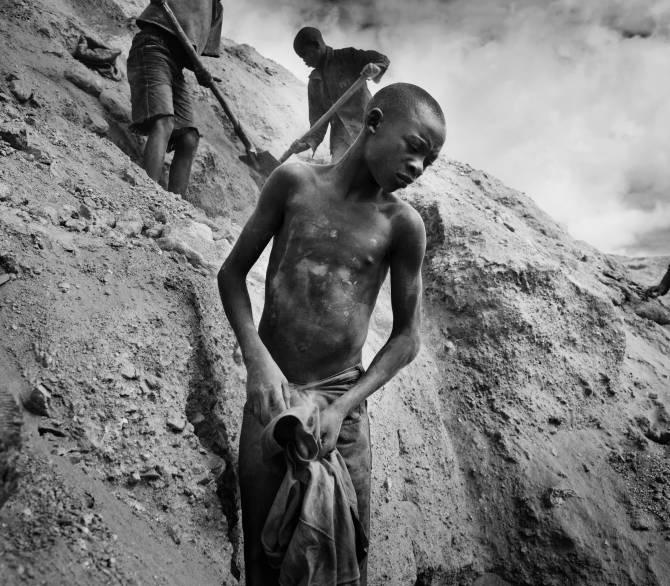 Boy stands on a hillside