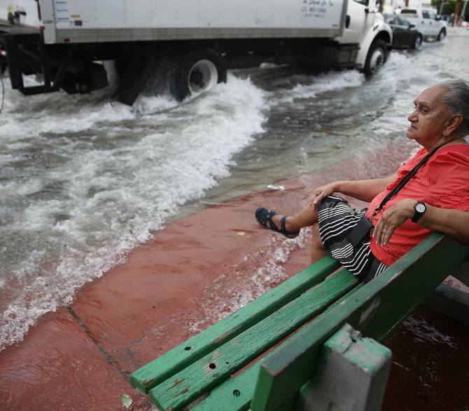 Mayabel Rents waits for a bus next to a flooded street that was caused by the combination of the lunar orbit which caused seasonal high tides and what many believe is the rising sea levels due to climate change on September 29, 2015 in Miami Beach, Florida. The City of Miami Beach is in the middle of a five-year, $400 million storm water pump program and other projects that city officials hope will keep the ocean waters from inundating the city as the oceans rise even more in the future.