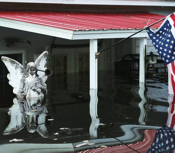 A statue and an American flag are seen outside a home flooded by water coming from the breached dams upstream as the water continues to reach areas in the eastern part of the state on October 9, 2015 in Andrews, South Carolina. The state of South Carolina experienced record rainfall amounts causing severe flooding and officials expect the damage from the flooding waters to be in the billions of dollars. (Photo by Joe Raedle/Getty Images)