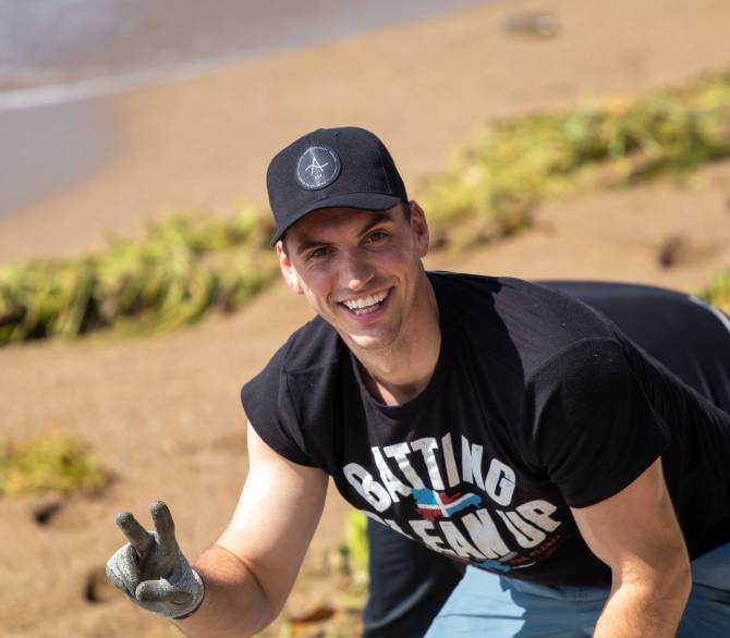 Brent Suter cleaning the beach in the Dominican Republic; Palm Creative