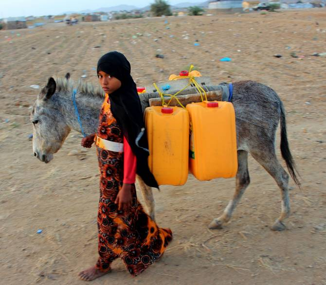 A girl walks with a donkey carrying jerry cans filled with water from a cistern at a make-shift camp for displaced Yemenis in severe shortage of water, in the northern Hajjah province on March 24, 2020; Getty