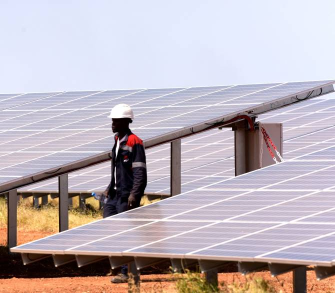 A technician walks through solar panels on October 22, 2016 during the opening ceremony of a new photovoltaic energy production site in Bokhol. Senegal; Getty