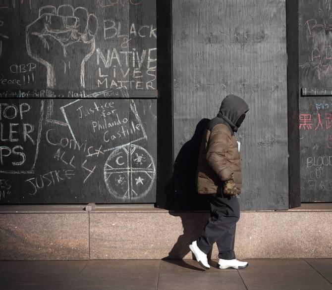 man walks by building with Black Lives Matter messages in chalk on the walls
