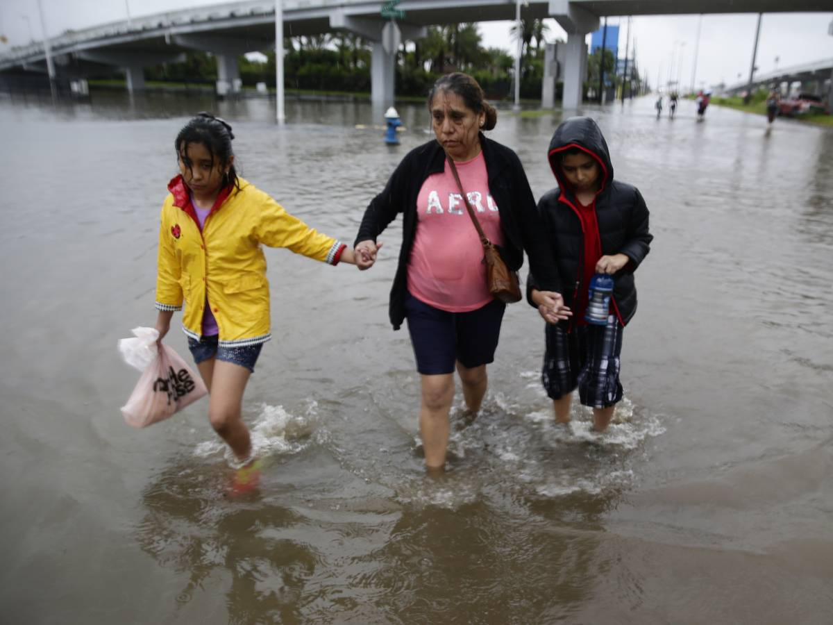 grandmother and two children wade through flood waters